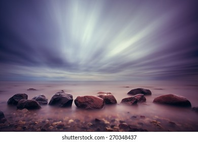 Backgrounds - smoked landscape with rocks on the beach and the peaceful sea.