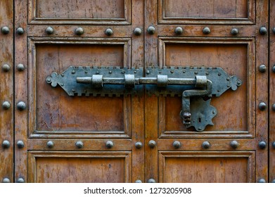 Backgrounds and textures: ancient wooden door, closed with traditional forged metal lock