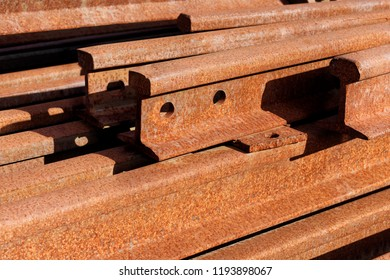 Backgrounds and textures: group of rusty steel rails, stacked in a pile outdoors, industrial abstract