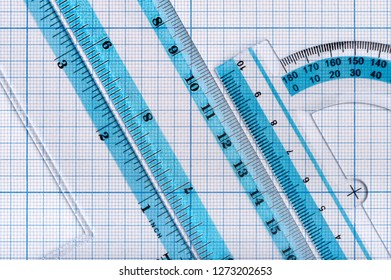 Backgrounds and textures: group of transparent plastic rulers, arranged on graph paper, educational abstract