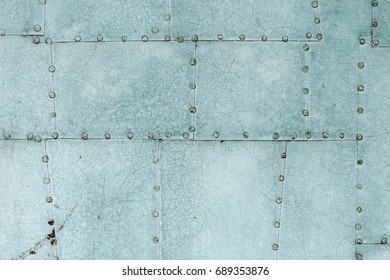 Backgrounds and textures: old painted riveted metal door close-up shot
