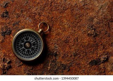 Backgrounds and textures: round magnetic compass on rough rusty map-like background