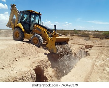 A backhoe being used to dump gravel into a trench at a construction site in Arizona. The driver is not visible, no model release is necessary.