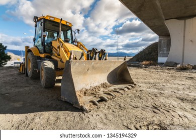 Backhoe building a section of a road