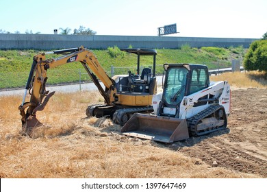 A backhoe and bulldozer parked in a dirt lot in Anaheim California