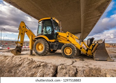 Backhoe in construction tasks of a road. Preparation of the land for the construction of a bridge on the highway