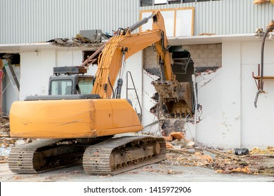 A backhoe demolishing a building, The bucket is in a hole in the wall of the building. Logos removed.