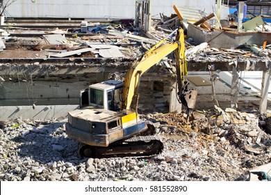 Backhoe destroying the building