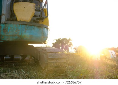 backhoe was digging a pit in the ground,a construction site excavator on blue sky with light, soft focus background