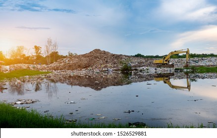 backhoe is lifting garbage at waste separation plant, Mountain large garbage pile and pollution,Pile of stink and toxic residue,These garbage come from urban and industrial areas can not get rid of