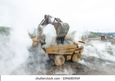 Backhoe load warm and smokey slag material into mining dump truck in Nickel Mining in South Sulawesi, Indonesia.