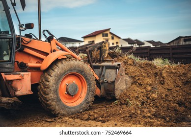 Backhoe loader close up. Portrait of engineer leveling earth and soil in garden