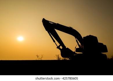 Backhoe loader on sunset