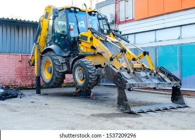 Backhoe loader stands leaning on a bucket. A man repairs a backhoe loader. Construction machinery in the city.