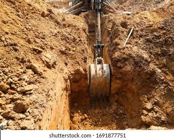 Backhoe-Maschine zum Ausgraben des Bodens für die Prüfkammer an der Baustelle.