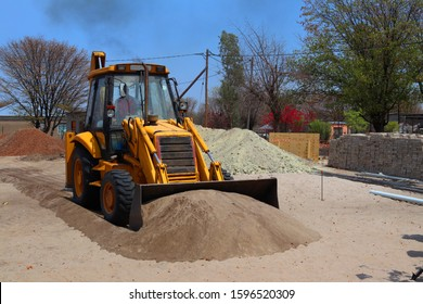 A backhoe pushing a pile of sand.This is a type of excavating equipment consisting of a tractor-like unit fitted with a loader-style shovel/bucket on the front and a backhoe on the back.