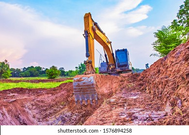 Backhoe, View of the backhoe was digging a pit in the ground. Large tracked excavator works in dig a pond. Backhoe excavator on construction site.