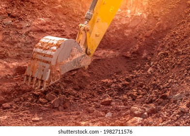 Backhoe working by digging soil at construction site. Bucket of backhoe digging soil. Crawler excavator digging on dirt. Closeup backhoe bucket of yellow backhoe. Earthmoving. Trenching machine.