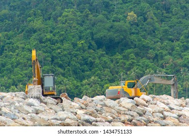 Backhoes are working to build a sea channel. Backhoes are scooping stones.
