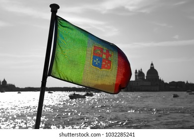 In backlight, the flag of the Italian navy sways aboard the ship on a desaturated background of the Venice lagoon and church.