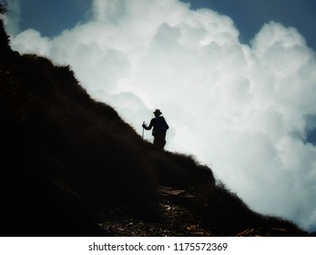 Backlight of hiker on the mountain with spectacular clouds