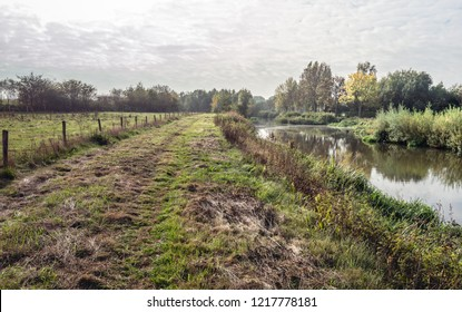 Backlight image of a rural area with wheel tracks in the mowed grass on the bank of the Dutch river Mark in the autumn season. Next to the grass is a long fence of barbed wire and wooden poles.