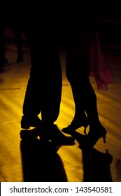 Backlight of the legs of two tango dancers