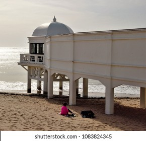 Backlight on the beach of La Caleta, Cádiz, Spain, with colonial building and unrecognizable person sunbathing,
