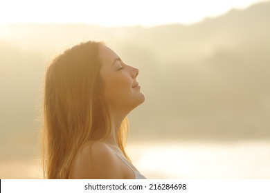 Backlight profile of a woman breathing deep fresh air in the morning sunrise isolated in white above