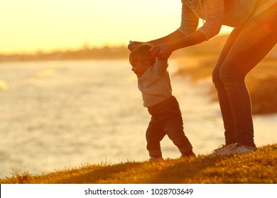 Backlight silhouette of a confident baby learning to walk and his mom helping him at sunset