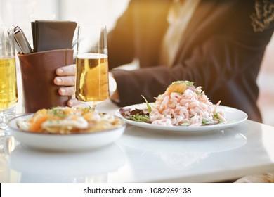 Backlight sun food man at restaurant shrimpsandwich and beer elegant luxury skybar