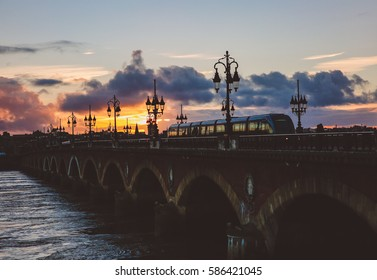 Backlight sunset on Pont de Pierre bridge over the river garonne in Bordeaux, France a UNESCO world heritage site with a tram passing by