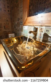 Backlight. Water flows into the golden sink from the tap.
