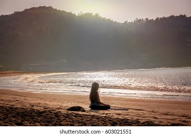 backlight of a woman practicing yoga sitting on the shore of the beach at sunset. Gokarna, India