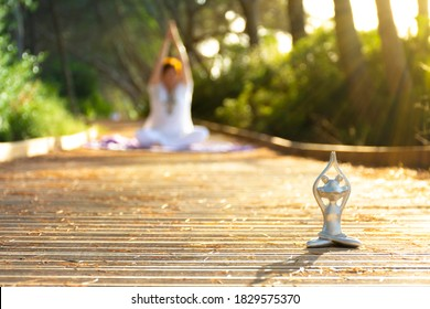 Backlight of a yoga frog figure at foreground and a defocused woman at background both in lotus meditating pose with hands above head, at sunset