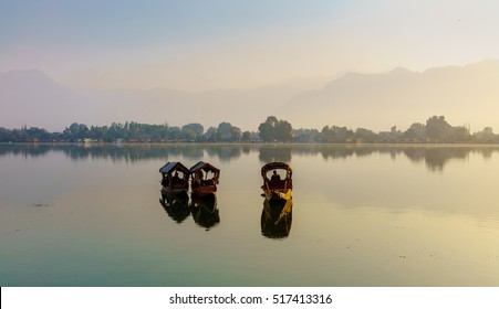 Backlit of 3 Shikara boats with their oar men as silhouette in the middle of the lake at dawn. The reflection in the water of boats and the blur shore. Mountain and trees are  in a blur background