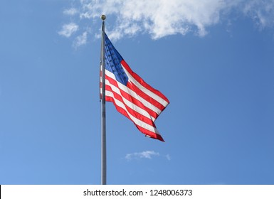 Backlit American flag on flagpole on a windy day against blue sky with light clouds