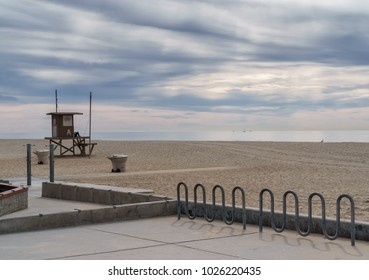 Backlit beach scene. Bike rack, lifeguard stand, sand, sea, sky, and clouds. Room for text.
