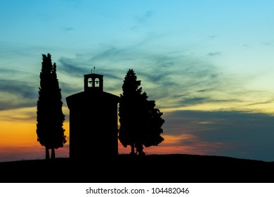 Backlit chapel with cypress trees in Tuscany near Pienza