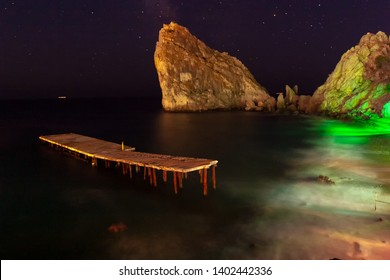 Backlit from the coast of colorful lanterns. Color image. Horizontal frame. Southern coast of Crimea. Summer night. The village of Simez, a rock in the sea. Diva. Long exposure shot