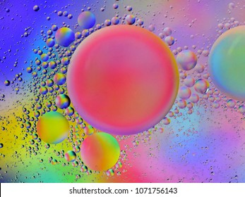 Backlit colorful oil droplets of different sizes floating on water.
