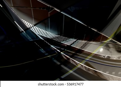 Backlit curvilinear ceiling and louvered wall panels in darkness. Tilt close-up photo of hi-tech interior. Modern architecture fragment in metallic colors.