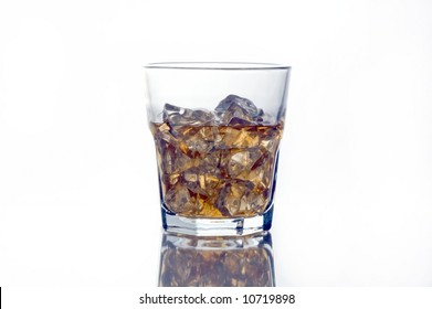 Back-lit glass of whiskey or scotch on reflective surface