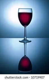 Back-lit glass of wine on reflective surface