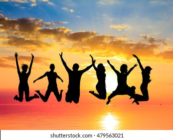 Backlit Group Jumping over Sunset