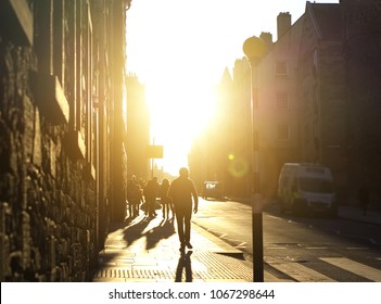 Backlit with heavy shadows - pedestrians in warm dress on a quiet town street in late evening with atmospheric glow effect