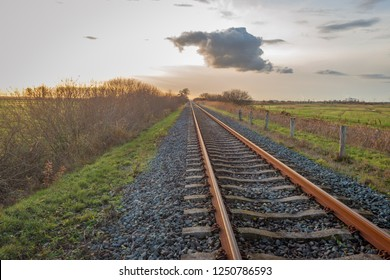 Backlit image of apparently endless long single rusty  rail tracks at sunset. The photo was taken at the end of a nice and sunny day in autumn near the Dutch village of Hooge Zwaluwe, North Brabant.