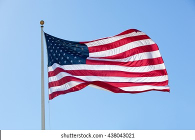 Backlit Large American Flag Waving in a Mild Wind, with Large Central Wave