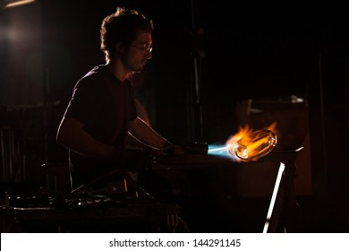 Backlit man with blowtorch shaping glass object