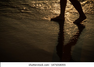 Backlit photograph of person enjoying a walk on a beach.